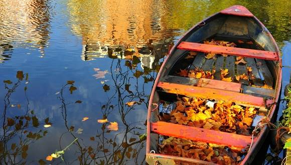 Wooden boat on canal in Amsterdam in Autumn