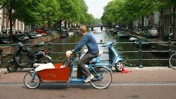 man riding bakfiets with child Amsterdam